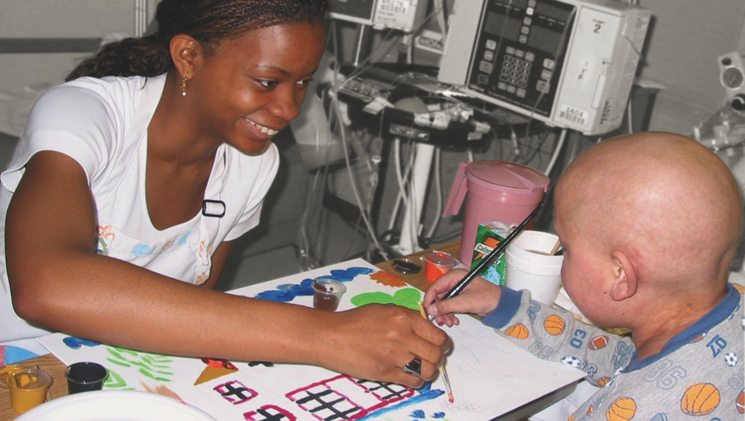 Art therapist painting with pediatric patient